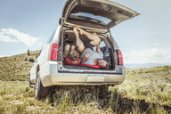 Mature man and teenage son getting out of off road vehicle, Bridger, Montana, USA - CUF17417