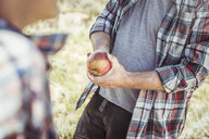 Cropped shot of father slicing apple with penknife for teenage son - CUF17420