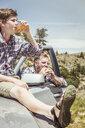 Teenage boy sitting on off road vehicle hood drinking juice, Bridger, Montana, USA - CUF17426