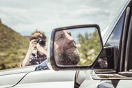 Teenage boy photographing father in off road vehicle, Bridger, Montana, USA - CUF17429