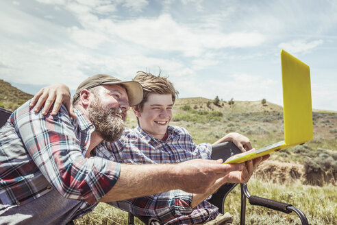 Man and teenage son sitting in camping chairs taking laptop selfie, Bridger, Montana, USA - CUF17432