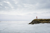 Woman standing by frozen lake, Holtsos, Iceland - CUF17441