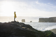Woman looking out over ocean, Kirkjufjara, Iceland - CUF17447