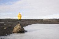 Woman on rock enjoying view, Solheimasandur, Iceland - CUF17453
