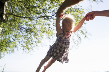 Father swinging baby girl in air, outdoors, low angle view - CUF17468