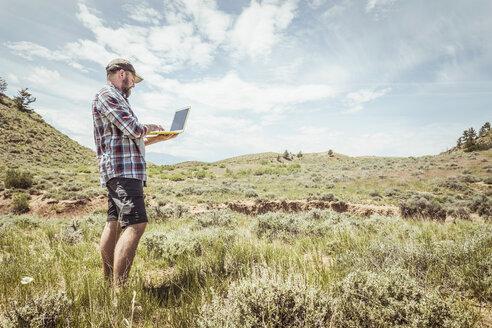 Man typing on laptop selfie in landscape, Bridger, Montana, USA - CUF17501