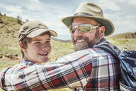 Portrait of man and teenage son looking over their shoulders in landscape, Bridger, Montana, USA - CUF17504
