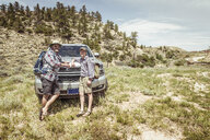 Portrait of man and teenage son on hiking road trip leaning on car hood in landscape, Bridger, Montana, USA - CUF17507