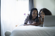 Lesbian couple lying on bed, using laptop - ISF06595