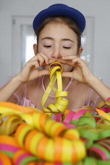 Girl wearing blue hat looking down blowing party streamers - CUF17719
