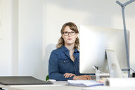 Young woman wearing eyeglasses sitting at desk using computer looking away smiling - CUF17788