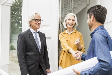 Architect holding rolled up blueprints shaking hands with homeowners at front door smiling - CUF17803