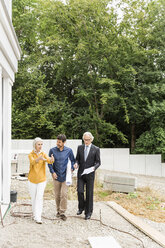 Full length front view of couple discussing housing redevelopment with architect - CUF17806