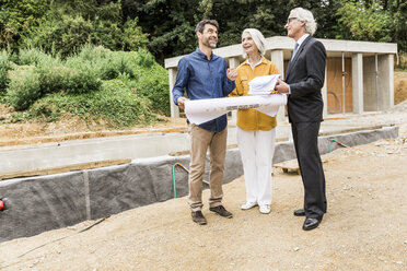 Couple on construction site discussing blueprints with architect smiling - CUF17809