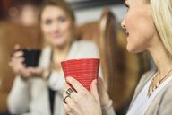 Cropped view of mid adult women face to face holding coffee cups smiling - CUF17818