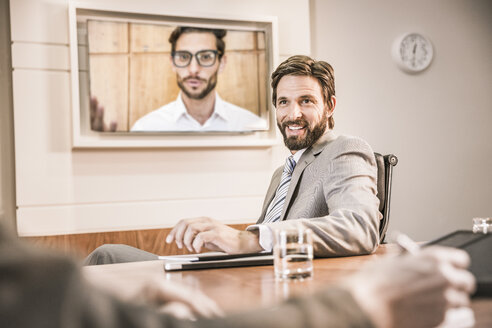 Business people in boardroom having video call meeting - CUF17995