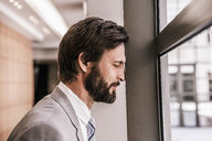 Side view of bearded businessman, eyes closed, head leaning against window frame - CUF18001