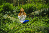Young woman practicing yoga in lotus position in forest - ISF06654