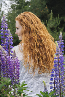 Rear view portrait  of young woman with long red hair  amongst purple wildflowers - ISF06735