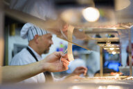 Chef checking order in traditional Italian restaurant kitchen - CUF18155