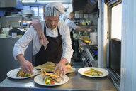 Chefs preparing dishes in traditional Italian restaurant kitchen - CUF18167