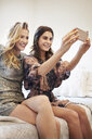 Two young women sitting on bed posing for selfie - CUF18230