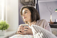 Young woman holding coffee cup on sofa gazing out of window - ISF06880