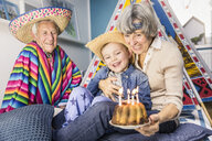Senior couple and grandson celebrating with birthday cake on living room floor - ISF06898