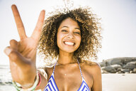 Happy woman showing peace sign on beach - CUF18301