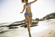 Woman jumping on beach - CUF18307