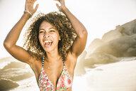 Happy woman raising arms on beach - CUF18334