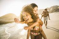 Parents giving children piggyback ride on beach - CUF18349