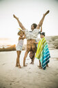 Family helping father with handstand on beach - CUF18364