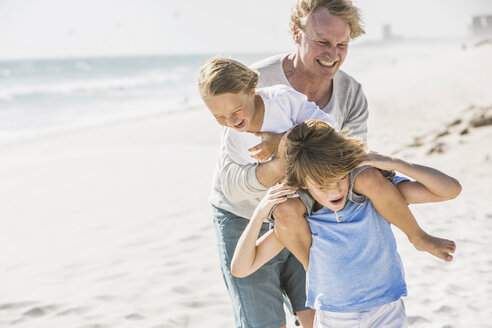 Father helping sons with piggyback on beach - CUF18376