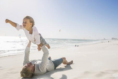 Father lying on beach lifting son - CUF18382