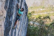 Rock climber climbing rock face, Thakhek, Laos - CUF18476