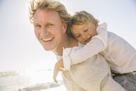 Father on beach giving son piggy back looking at camera smiling - CUF18608