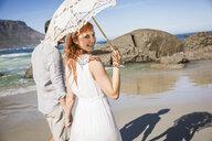 Couple holding hands, walking on coastline holding umbrella looking over shoulder at camera smiling - CUF18641