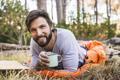 Portrait of man in sleeping bag with coffee in forest, Deer Park, Cape Town, South Africa - CUF18788
