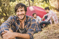 Happy mid adult man and friends camping in forest, Deer Park, Cape Town, South Africa - CUF18818
