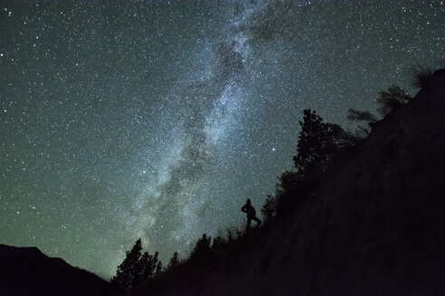 Man silhouetted against night sky and milky way in mountain forest, Penticton, British Columbia, Canada - ISF07097