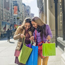 Young female adult twins looking into shopping bags outside city shop - ISF07100