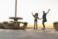 Couple using rollerskates and skateboard, holding hands, smiling - ISF07151