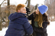 Young couple petting dog in snowy Central Park, New York, USA - ISF07225