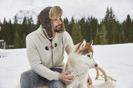 Young man wearing trapper hat petting husky in snow, Elmau, Bavaria, Germany - CUF18950