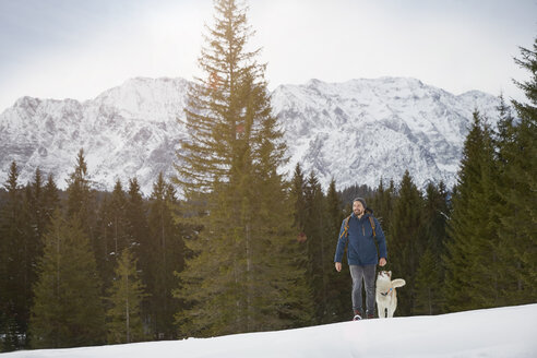 Young man walking uphill with husky in snow covered landscape, Elmau, Bavaria, Germany - CUF18962