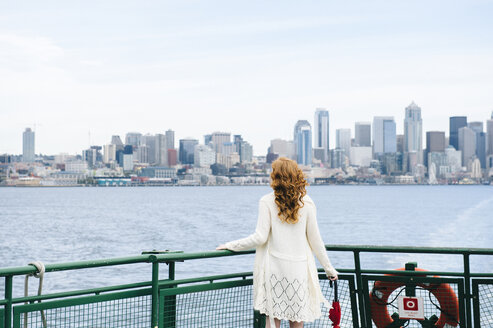 Rear view of woman looking at city skyline from passenger ferry on Puget Sound, Seattle, USA - ISF07264