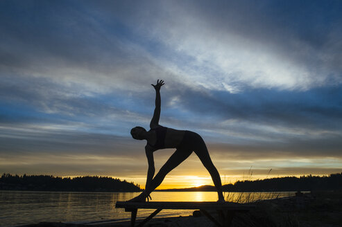 Woman practising yoga by lake at sunset - ISF07273