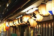 Row of illuminated paper lanterns at night, Tokyo, Japan - ISF07318