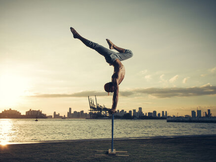 Mature man doing handstand on pole, South Pointe Park, South Beach, Miami, Florida, USA - ISF07336